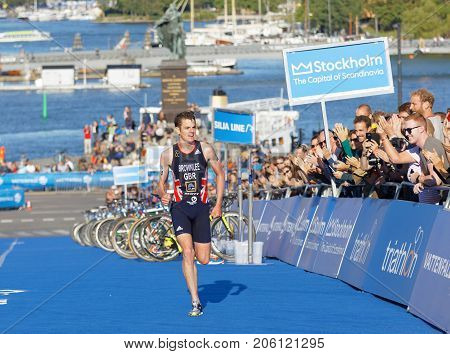 STOCKHOLM - AUG 26 2017: Running triathletes Jonathan Brownlee and smiling hand clapping audience in the background in the Men's ITU World Triathlon series event August 26 2017 in Stockholm Sweden