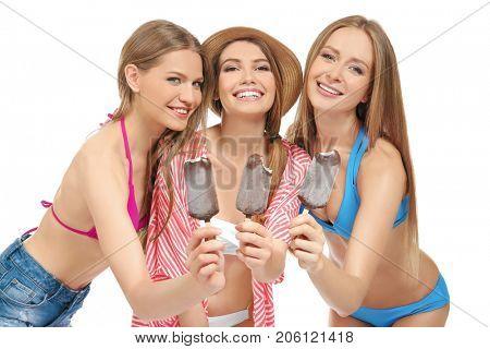 Beautiful young women in beachwear eating ice-cream on white background