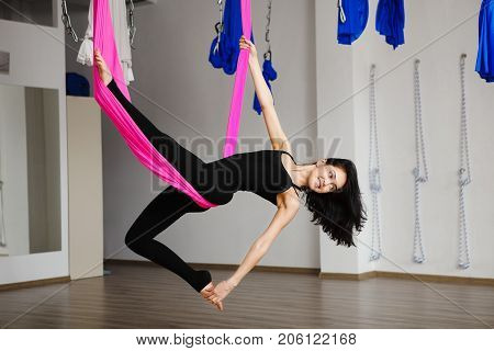 Top view on young female person in back sport suit doing aerial yoga exercises in pink hammock. Anti-gravity sport exercise, keeping balance on hanging material