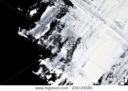 Brush strokes of white oil paint on black background - abstract composition and space for text