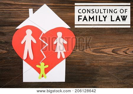 Paper figures of parents with child and broken heart on wooden background. Consulting of family law