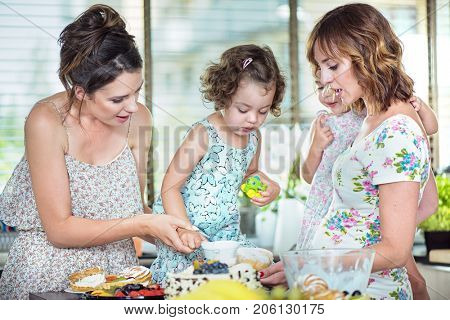 Two women cooking with their daughters in the kitchen