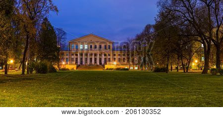 Panoramic night view of park lawn and building of State University of Communication in Yusupov Garden Saint Petersburg Russia