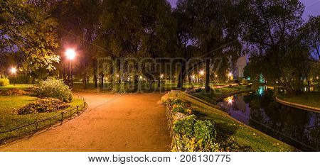 Panoramic night view of park pond and footpath in Yusupov Garden Saint Petersburg Russia
