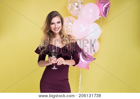 Self-confident girl with glass of champagne. Beautiful girl in studio smile and happy. Christmas party. Happy New Year 2018!
