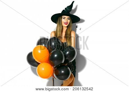 Halloween Party girl. Happy Halloween Sexy Witch with Air balloons. Beautiful young surprised woman in witches hat and costume holding black and orange air balloons. Isolated on white background