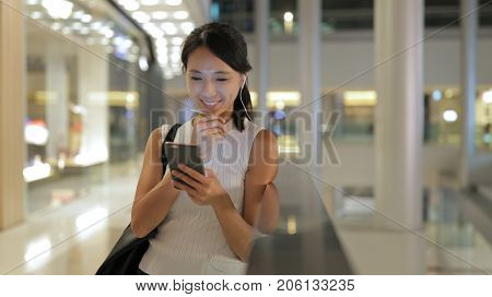 Woman using smart phone in the mall