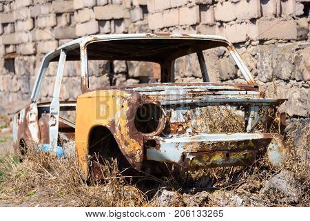 ARARAT PROVINCE, ARMENIA - APRIL 4: Abandoned and rusty skeleton of a Soviet Russian car growing hay inside by the side of the building exterior April 4, 2017 in Ararat Province, Armenia.