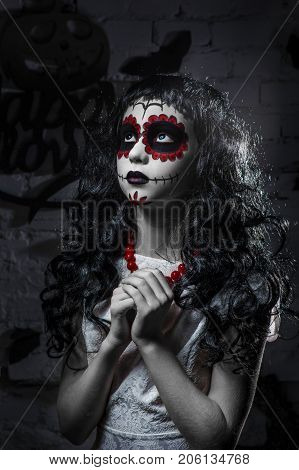 Little santa muerte girl with black curly hair is looking at the top with hands laid in prayer