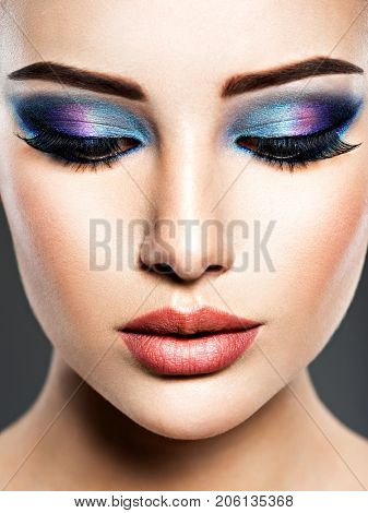 Portrait of a woman with beautiful fashion makeup. Blue bright color
