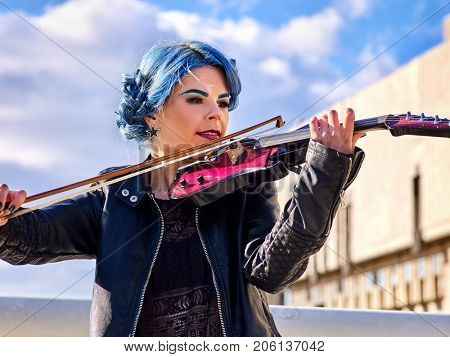 Woman perform music on violin in park outdoor. Girl performing jazz on city street. Spring outside with blue hairstyle background. Street musician makes money for a living.