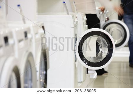 Washing machines, dryer and other domestic appliance equipment in the store. focus at equipment, defocused unrecognizable customer at background.