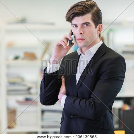 Portrait of hansome business man in office talking on mobile phone and looking at camera