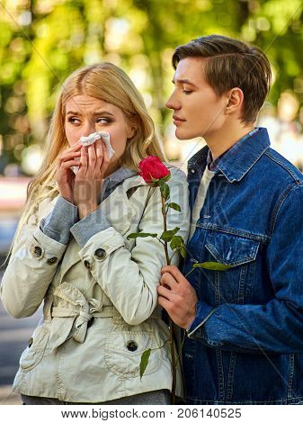 Autumn couple walking park. First date in good weather day. Betrayal and forgiveness of girl is crying with handkerchief on outdoor. Man apologizes and gives rose flowers. Guy comforts crying girl.