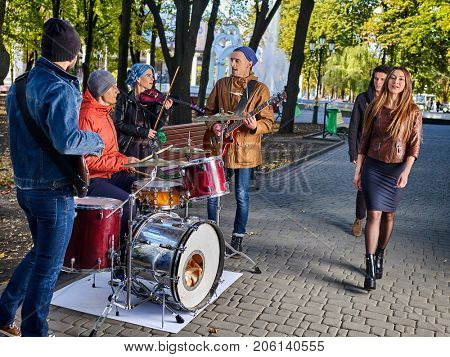 Festival music band. Friends playing on percussion instruments in autumn city park. Fountain and trees in background. People like street music.