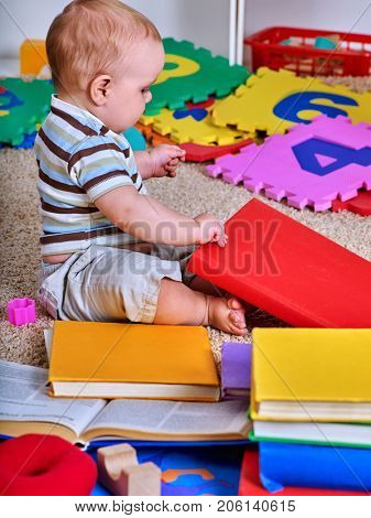 Child jigsaw develops children. Kid puzzle making baby. Little boy holding big pieces. Playing on floor in kindergarten. Little genius with books.