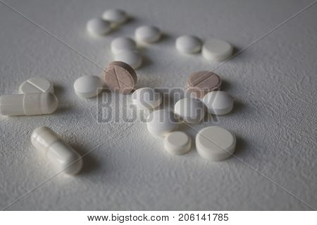 Scattered different pills and capsules close up on a white background. Selective focus. copy space. concept of medicine and drugs.