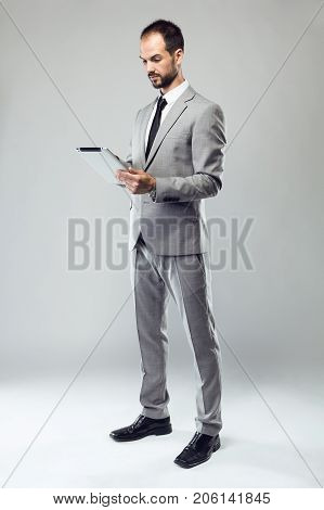 Business Young Man Using His Digital Tablet Over Gray Background.