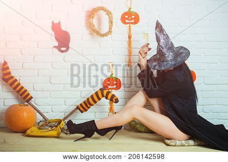 Halloween woman in witch hat and coat sitting on floor. Girl with pumpkins striped stockings black cat on wall. Evil spell and magic. Tradition and traditional symbols. Holiday celebration concept.