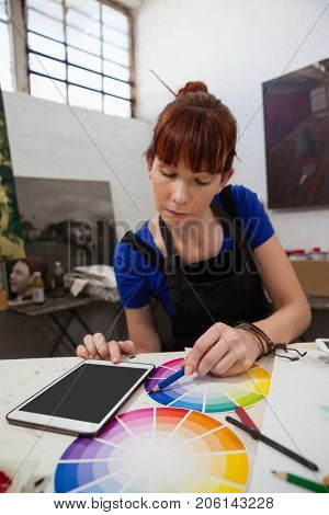 Beautiful woman matching color with color swatch at table