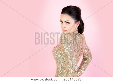 Woman in party dress with golden sequins. Girl with brunette hair on pink background. Fashion and style. Beauty and makeup. Holidays birthday new year christmas anniversary celebration copy space