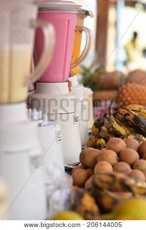row of blenders with fresh smoothies and fruits nearby