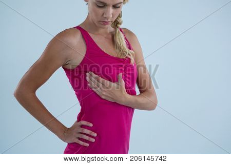 Young woman touching breast for lupms while standing against gray background