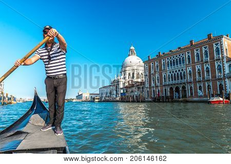 Venice, Italy - September 2017: Gondolier with an oar in Venice. Gondolier sail on a Venetian canal to the Grand canal, Italy