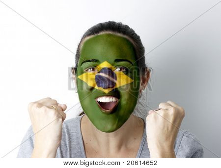Brasilian fan screaming GOAL with hands up and painted flag on her face.