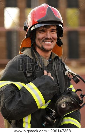 Portrait of smiling fireman wearing fire fighter turnouts, red helmet and breathing apparatus, closeup