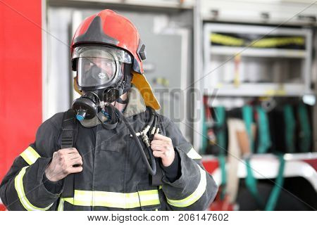 Portrait of fireman wearing fire fighter turnouts and red helmet with breathing apparatus