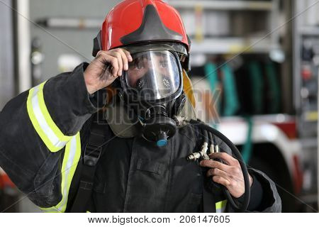 fireman wearing fire fighter turnouts and red helmet with breathing apparatus on background of fire truck, hand on helmet visor