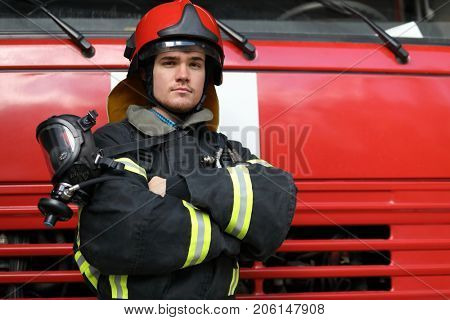 Portrait of fireman wearing fire fighter turnouts and red helmet, fold ones arms