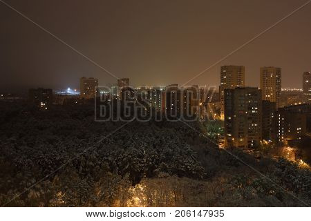 snow in spring in Moscow, city landscape from window of multi-storey building, evening