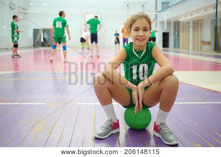 Pretty girl in green sits on ball in gym during volleyball game, playing people out of focus