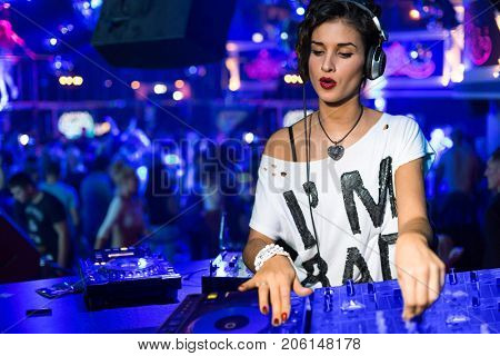 Collage with woman DJ turns records at club under blue light