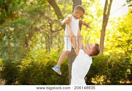 Young man playing with adopted African American boy outdoors