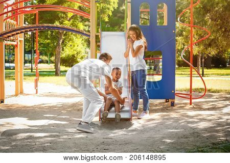 Young family with adopted African American boy on playground