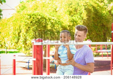 Young father with adopted African American boy on the sports ground
