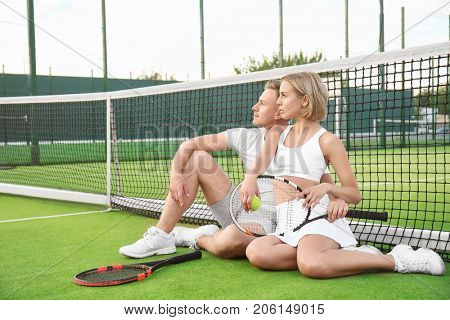 Young couple with tennis rackets sitting on court