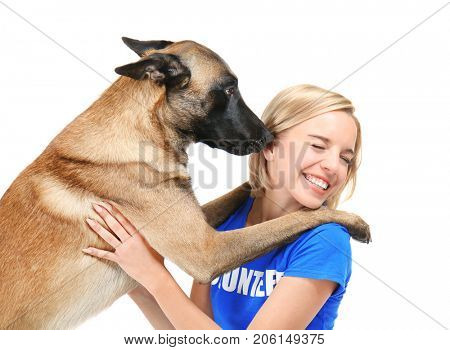 Dog licking young female volunteer, isolated on white. Concept of volunteering and animal shelters