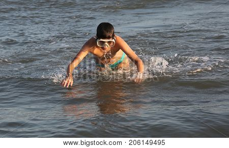 happy child plays diving in the sea wearing a diving mask