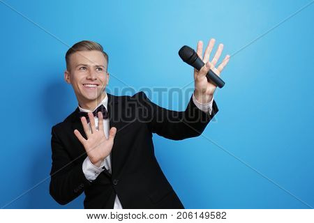 Young presenter with microphone on color background