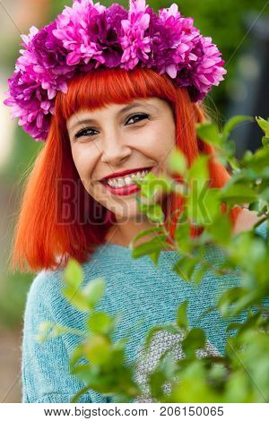 Attractive red haired girl with wreath of flowers in a park