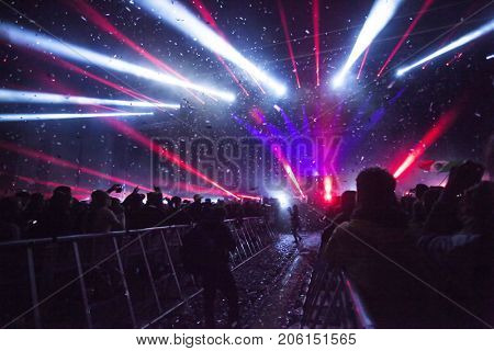 Crowd at concert - Cheering crowd in front of bright colorful stage lights and confetti