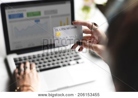 Woman Hand Holding Platinum Credit Card with Laptop Background
