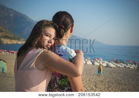 Daughter teenager hugs her mother by the shoulders, Outdoors by the sea