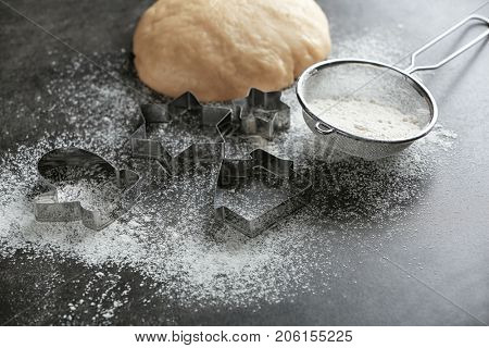 Composition with dough and cutters for Christmas cookies on table