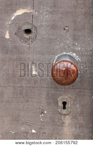 Details of an old wooden door with an antique knob. The focus is on the doorknob.