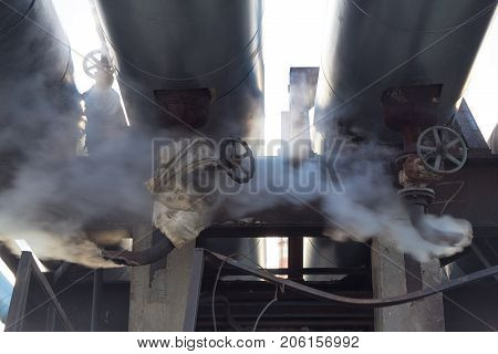 Leakage of steam in heat pipeline. Steam outgoing from the rusty tube with valve